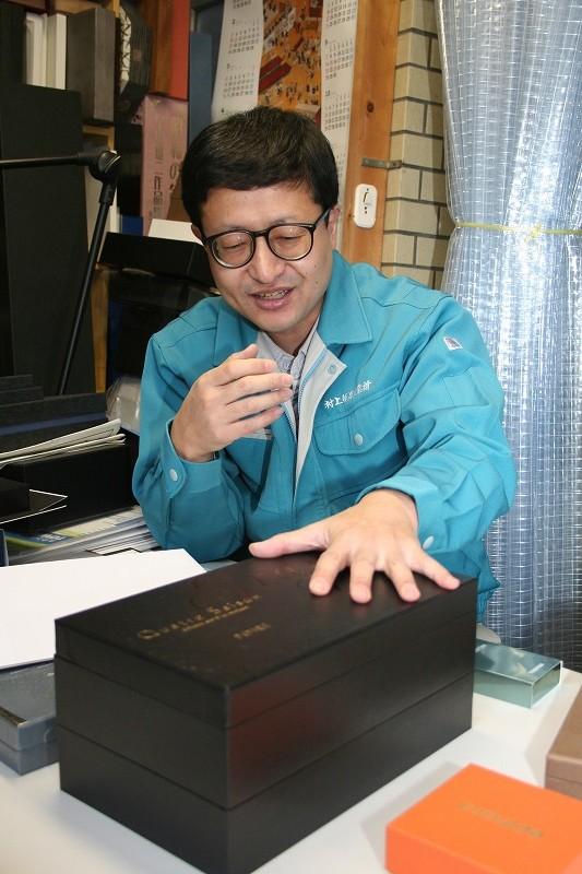 お菓子屋さん用に製作した貼箱を説明する村上氏