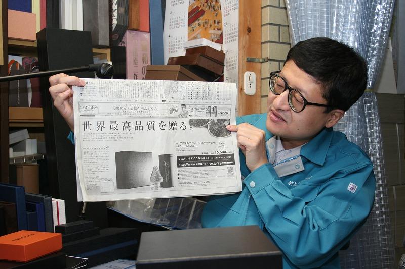コーヒー用の貼箱が広告として掲載された新聞を説明する村上氏